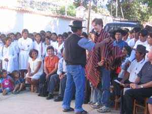 Brendan Sherar, Vice-President of BiblioWorks, receives a traditional poncho from the town mayor.
