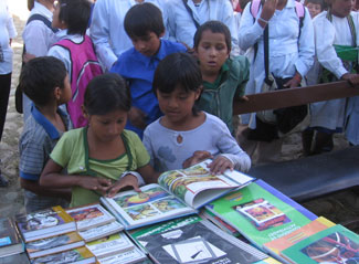 Kids surrounding the tables full of books to be donated to their new library.